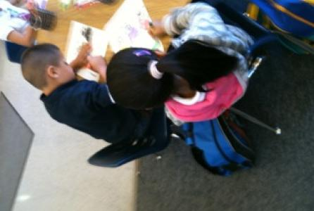 Image of Students take to writing from an early age.   These Kinder students work diligently as they write a sentence.